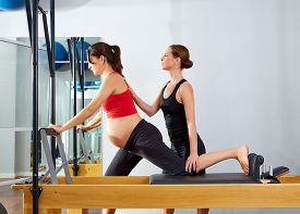 stock photo of pilates  - pregnant woman pilates reformer cadillac exercise workout with personal trainer - JPG