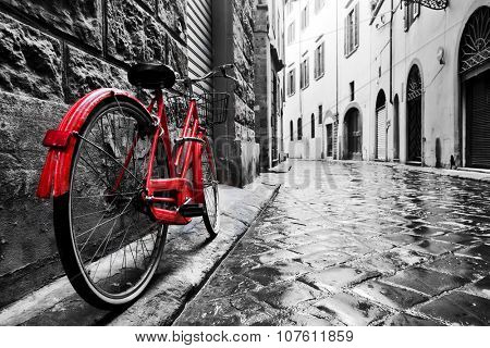 Retro vintage red bike on cobblestone street in the old town color in black and white old charming bicycle concept poster id 107611859