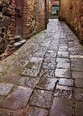 image of porphyry  - old narrow alley in tuscan village - antique lane with pavement of stone - tuscany italy