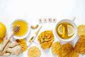 Wooden Word Sick, Tea With Lemon, Thermometer, Ginger, Honey, Tablets And Dry Leaves On A White Back poster
