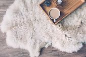 Mug with coffee and home decor on wooden serving tray on sheep skin rug. Winter weekend concept, top poster
