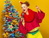 Woman Near Christmas Tree With Microphone Singing poster