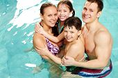 pic of swimming pool family  - Cheerful family in swimming pool smiling at camera - JPG