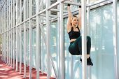 Photo of energetic young woman 20s wearing tracksuit doing workout with horizontal metal bar on spor poster
