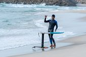 A Middle Aged Man Is Finishing Some Foil Surfing Or Hydrofoil Surf Training In The Sea. poster