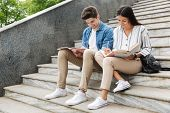 Photo of young amazing loving couple students colleagues outdoors outside on steps reading book writ poster