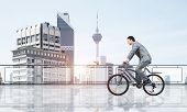 Man Wearing Business Suit Riding Bicycle On Penthouse Balcony. Handsome Cyclist On Background Of Cit poster