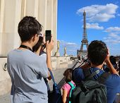 Young Caucasian Tourists Take Pictures Of Eiffel Tower In Paris France From Trocadero Quartier poster