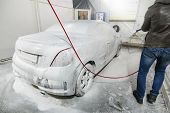 Male Worker Wash The Car With High Pressure Washer. Car Wash With Foam In Car Wash Station. A Man Sp poster