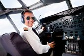stock photo of work crew  - Male pilot sitting in an airplane cabin flying and smiling - JPG