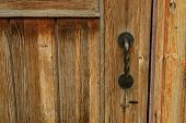 Metal Handle On A Brown Wooden Door. Black Wicker Handle On The Old Door. Metal Handle On A Brown Wo poster