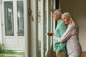 Side view of active senior Caucasian woman embracing senior man near door at home poster