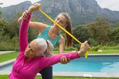 Front view of Caucasian female trainer assisting active senior Caucasian woman to exercise with resi poster