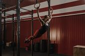 Young Woman Swinging On Gymnastic Rings. Female Athlete Doing Muscle-ups Exercise On Rings At The Gy poster