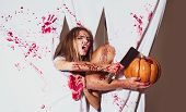 Halloween Nightmare. Pretty Girl Cutting Halloween Pumpkin With Axe. Sexy Woman Dirty With Blood Sta poster