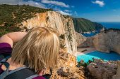 Blond Female Tourist Standing On The Edge Of A Cliff And Photographing The Stunning Cliffs In Shipwr poster