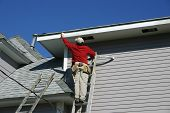 image of soffit  - a worker atop a tall ladder paints a fascia board on a house - JPG