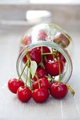 image of picking tray  - Freshly picked ripe cherries with stem and leaves in front of a preserving jar filled with cherries - JPG