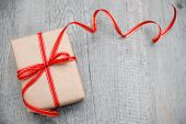 stock photo of bowing  - Gift box with red bow on wood background - JPG