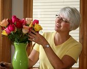 pic of one dozen roses  - Pretty gray haired woman admiring her rose bouquet - JPG