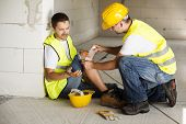 stock photo of hurt  - Construction worker has an accident while working on new house - JPG