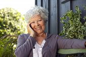 image of bench  - Happy elderly woman sitting on a bench in backyard talking on mobile phone and smiling - JPG
