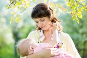 Young Mother Breast Feeding Her Baby Girl Outdoors