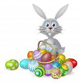 stock photo of ester  - White Easter bunny rabbit with a basket of colorful chocolate Easter eggs - JPG