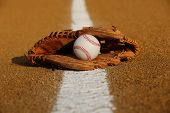 stock photo of infield  - New Baseball in a Glove in the Infield - JPG
