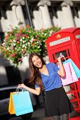 London shopping woman happy excited holding shopping bags by red phone booth. Female shopper smiling