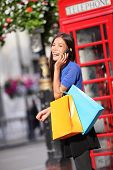London woman talking happy on smart phone shopping while laughing on mobile phone holding shopping b