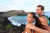 Постер, плакат: Hiking travel couple tourist on Hawaii hike Tourist backpackers walking on Green Sand Beach Papa