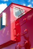 stock photo of caboose  - Detail of red train caboose against blue sky - JPG