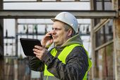 image of substation  - Electrician with cell phone in the electric substation - JPG
