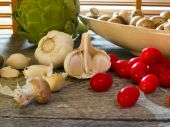 stock photo of crimini mushroom  - Garlic with cherry tomatoes crimini mushrooms and an artichoke by kitchen window  - JPG
