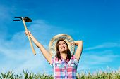 picture of hoe  - Successful female farmer raising hoe in corn field and smiling - JPG