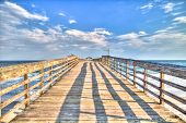 stock photo of long beach  - Fishing pier juts over the Atlantic Ocean - JPG