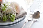 stock photo of buttercup  - Festive wedding elegant dining table setting with a bouquet of flowers buttercups and white lilac and vintage cutlery on a white table - JPG