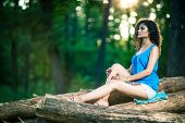Beautiful Young Woman Sitting On Log Posing
