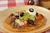 stock photo of shredded cheese  - A tostada with shredded beef cheese refried beans and sour cream - JPG