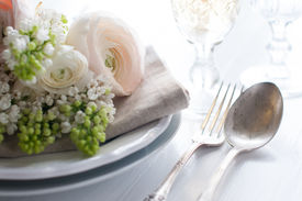 foto of buttercup  - Festive wedding elegant dining table setting with a bouquet of flowers buttercups and white lilac and vintage cutlery on a white table - JPG
