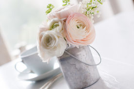 image of buttercup  - Little delicate elegant bouquet of flowers buttercups and white lilacs in tin can and a teacup on white wooden table morning breakfast - JPG