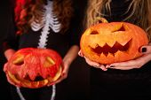 stock photo of antichrist  - Photo of carved Halloween pumpkins held by females - JPG