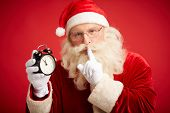 pic of shhh  - Santa Claus holding clock showing five minutes to midnight and making shhh gesture - JPG