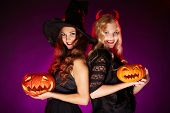 stock photo of repentance  - Portrait of two happy females with carved Halloween pumpkins - JPG