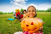 foto of happy halloween  - Happy African girl holds Halloween pumpkin and smiles with her friends on background - JPG