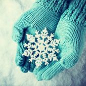 picture of wonderful  - Female hands in light teal knitted mittens with sparkling wonderful snowflake on a white snow background - JPG