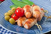 stock photo of bacon strips  - Grilled sausages wrapped in strips of bacon with tomatoes and sage leaves - JPG