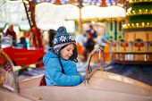 foto of funfair  - Adorable little boy on a carousel at Christmas funfair or market outdoors