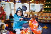 stock photo of funfair  - Adorable little child on a carousel at Christmas funfair or market outdoors